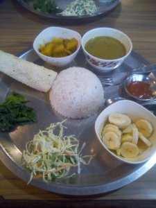 dal bhat, rice , papadam, bitter spinach, dhal soup, cabbage, and a side of banana